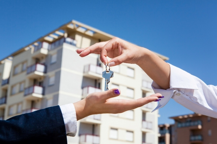 real estate agent passing the key to the client