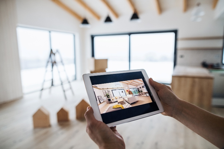 A hand holding a tablet displaying a house design