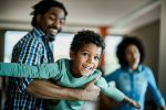 Happy African American boy having fun with his father at home